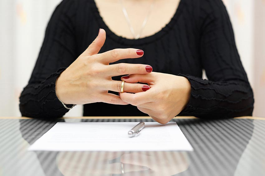 Woman Finalizing Divorce by Taking Ring Off