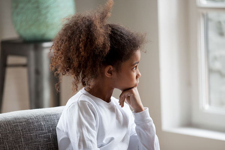 Child looking out the window thoughtfully