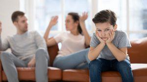 A unhappy boy with parents arguing about high conflict divorce case