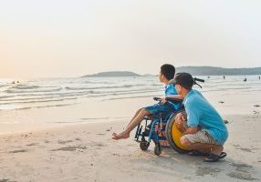 A special needs child in wheelchair and parent going at the beach